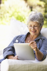 Portrait Of Senior Woman Using Digital Tablet At Home